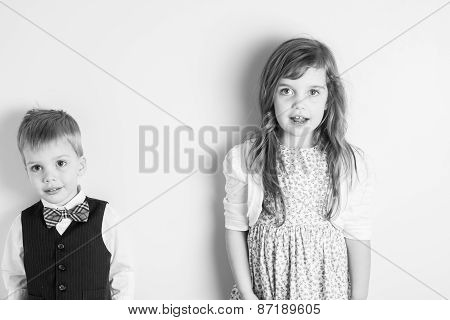 Black And White Portrait Of Brother And Sister Standing Against A Wall
