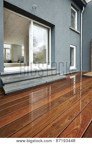 Wet Outdoor Wood Surface In Front Of A Renovated Wall