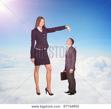 Small businessman looking up at large woman in suit