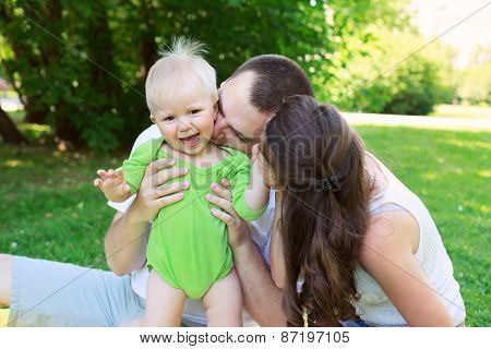 Happy Family Outdoors  Mum And Dad Hold And Kiss Baby