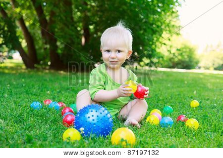 Cute Kid Baby Boy Sitting On Grass Playing With Balls