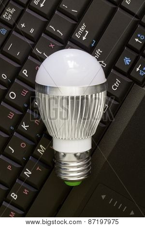 Close up Led Bulb at the keyboard background.