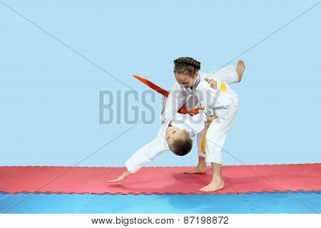 Little girl rolls boy on the mats