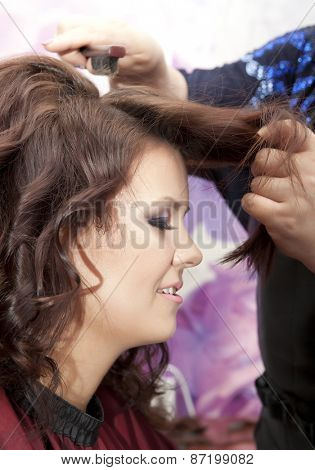 Side view of hairdresser combing hair of female customer before haircut
