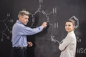 stock photo of professor  - Professor of chemistry writes on the blackboard formula together with his student - JPG