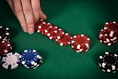 stock photo of poker hand  - dealer hands out red poker chips close up - JPG