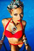 stock photo of turban  - Beautiful fashionable woman near the pool wearing colored turban - JPG