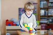 picture of indoor games  - Little blond kid boy playing with lots of colorful plastic blocks indoor - JPG