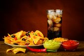 picture of nachos  - nachos plate salsa chesse and guacamole dip and cola drink - JPG