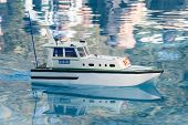 foto of sloop  - White yacht mini with its reflection in the water - JPG