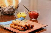 foto of condiment  - Grilled brats on a stacked on a plate ready to serve with condiments ketchup and mustard and buns - JPG