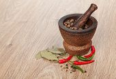 stock photo of peppercorns  - Mortar and pestle with red hot chili pepper and peppercorn on wooden table - JPG