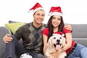 stock photo of dog christmas  - Studio shot of a young couple and their dog wearing Santa hats and celebrating Christmas seated on the floor next to a modern grey sofa isolated on white background - JPG