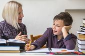 stock photo of tutor  - Junior student does homework with the help of his tutor - JPG