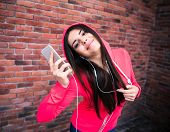 foto of sportive  - Happy sportive cute woman listening music on smartphone over brick wall - JPG