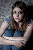 image of self-torture  - Top view of young woman crying and looking at camera while sitting against dark wall - JPG