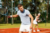 stock photo of concentration man  - Handsome young man holding tennis racket and looking away while standing on tennis court and with woman in the background - JPG
