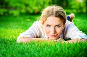 picture of lie  - Beautiful happy woman lying on a grass outdoor and smilng - JPG