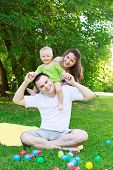 foto of mums  - Happy family outdoors mum and dad hold baby playing with colorful balls sitting on grass - JPG