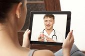 stock photo of video chat  - Woman having video chat with doctor on laptop at home - JPG