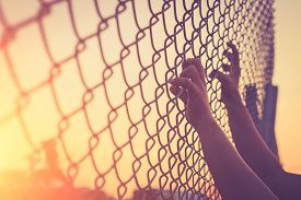 pic of safety barrier  - Hand holding on chain link fence Vintage filter effect - JPG