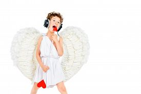image of cupid  - Cheerful little boy in a costume of angel listening to music in headphones and singing - JPG