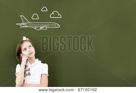 Cute girl of school age standing at blackboard