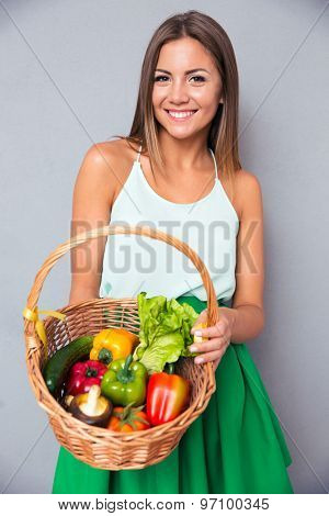 Portrait of a smiling young woman holding basket with vegetables over gray background