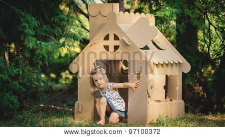 girl playing cardboard house in a city park