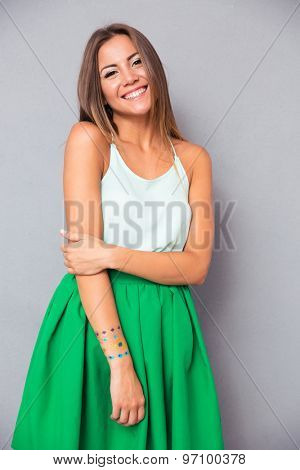 Portrait of a happy pretty woman standing over gray background