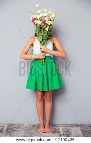 Full length portrait of a young woman covering her face with flowers on gray background