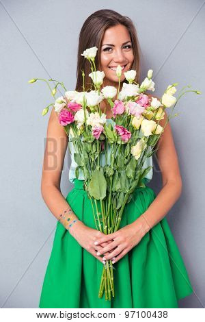Portrait of a cheerful pretty woman holding flowers over gray background. Looking at camera