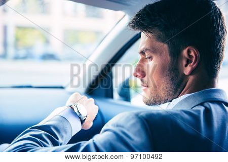 Handsome businessman looking on wrist watch in car