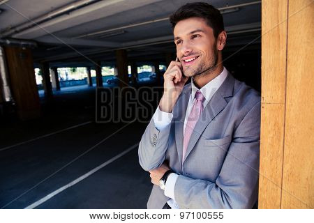 Smiling businessman talking on the phone in underground parking