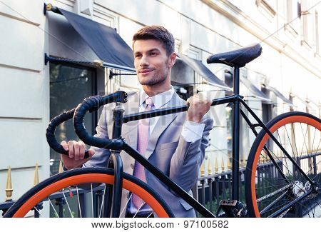 Handsome businessman carrying his bicycle on city streets
