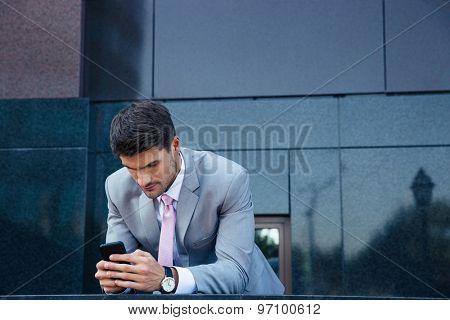 Confident businessman using smartphone outdoors