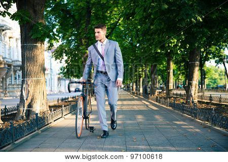 Handsome businessman walking with bicycle on the street in town