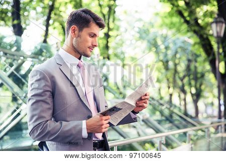Handsome businessman reading newspaper outdoors