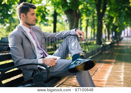 Portrait of a pensive businessman sitting on the bench outdoors in park and holding tablet computer