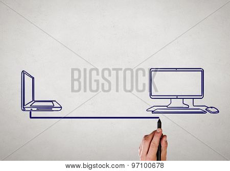 Close up of male hand drawing connection between laptop and computer