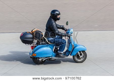 Blue Vespa Scooter On The Road