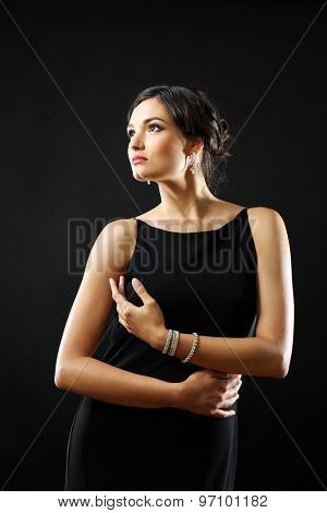 Pretty woman in black dress on dark background