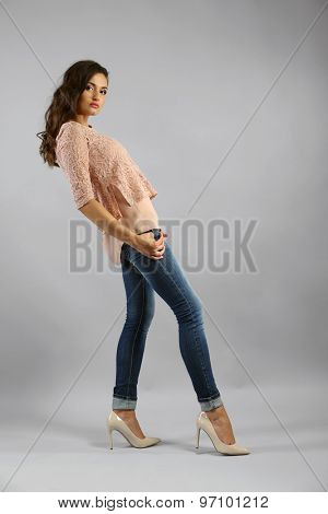 Young pretty woman on grey background