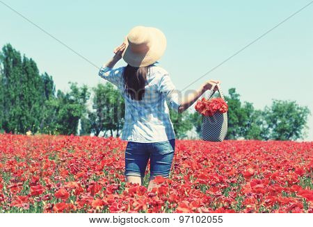 Woman walking with bag on poppy field over blue sky background