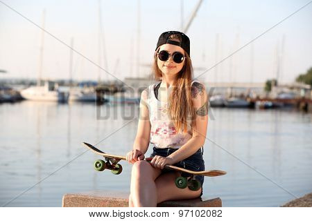 Beautiful tattooed girl with skateboard, outdoors