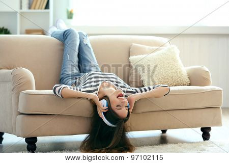 Woman listening music in headphones while lying on sofa in room