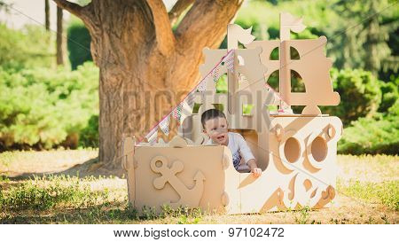Boy playing in cardboard boat at park.