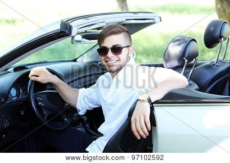 Pretty young man in cabriolet, outdoors