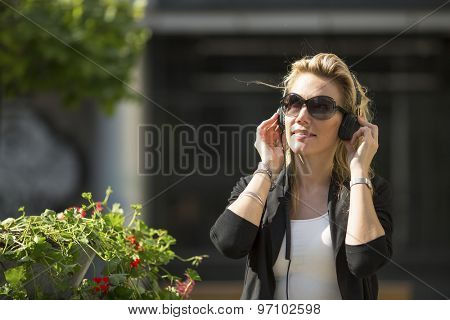 Attractive blond woman enjoying music in headphones outdoors.