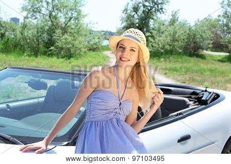 Pretty girl standing near cabriolet, outdoors